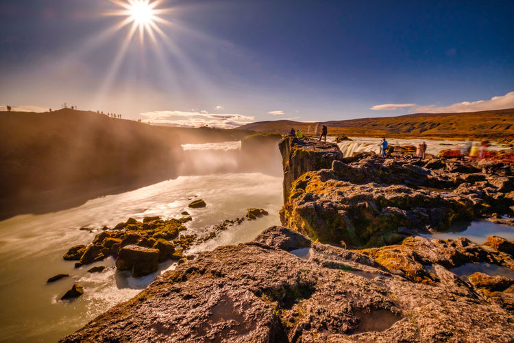 Goðafoss in long exposer, blue sky, warm autumn colors in the sun