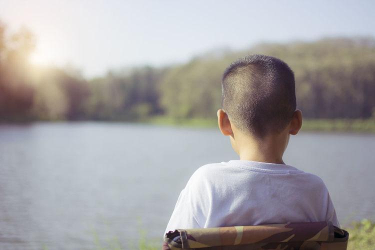 Rear view of boy looking at lake