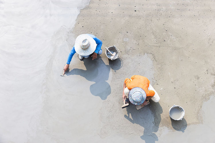 Directly above shot of workers leveling cement on footpath