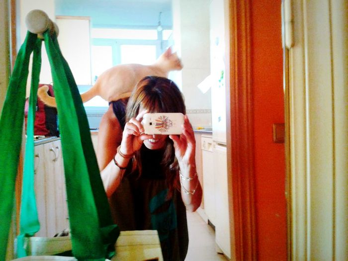 Young woman clicking herself with camera phone