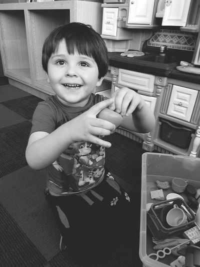 Smiling boy holding toy at home