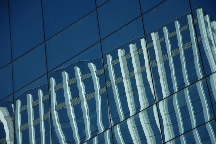 Low angle view of modern glass building in city against sky