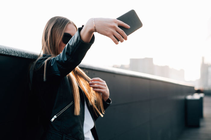 Pretty woman with long hair makes selfie on mobile Hair Architecture One Person Casual Clothing Urban Hairstyle Technology Lifestyles Selfie Copy Space Mobile Photography Communication Wireless Technology Activity Women Young Adult Long Hair Holding Using Technology Black Clothes Fashion Blogger Golden Hair  Golden Hour Leather The Modern Professional