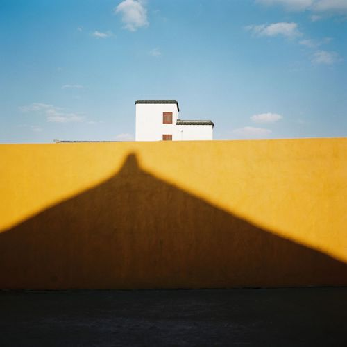 Shadow on surrounding wall against sky