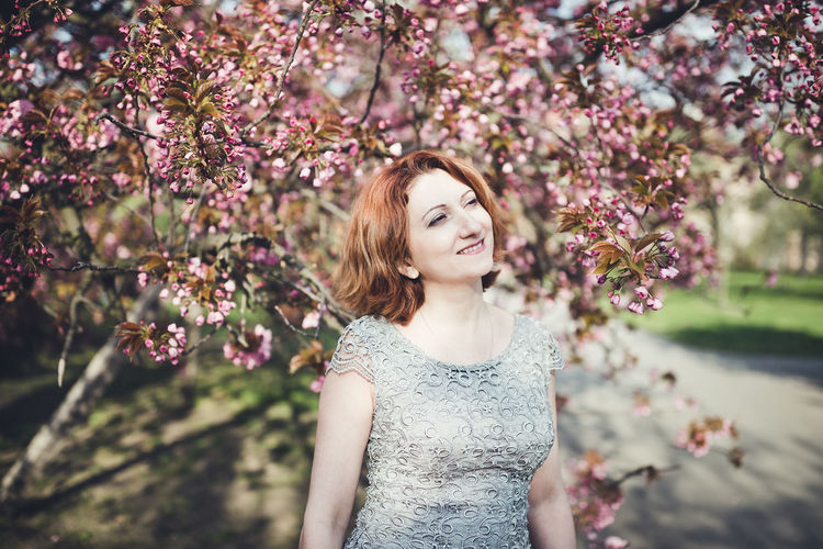 Portrait of beautiful young woman standing by flowering tree