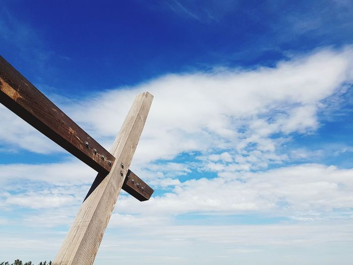 Low angle view of cross sign against blue sky