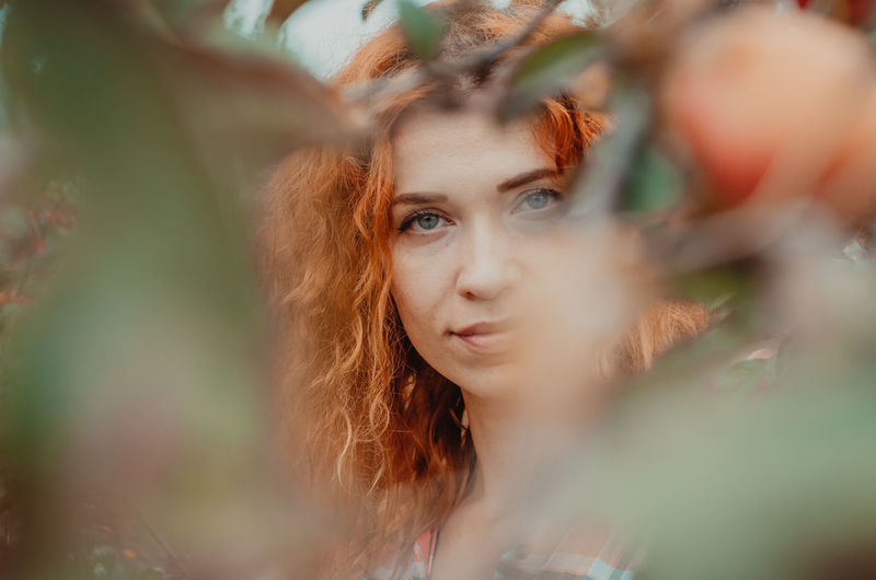 Portrait of woman seen through fruit tree