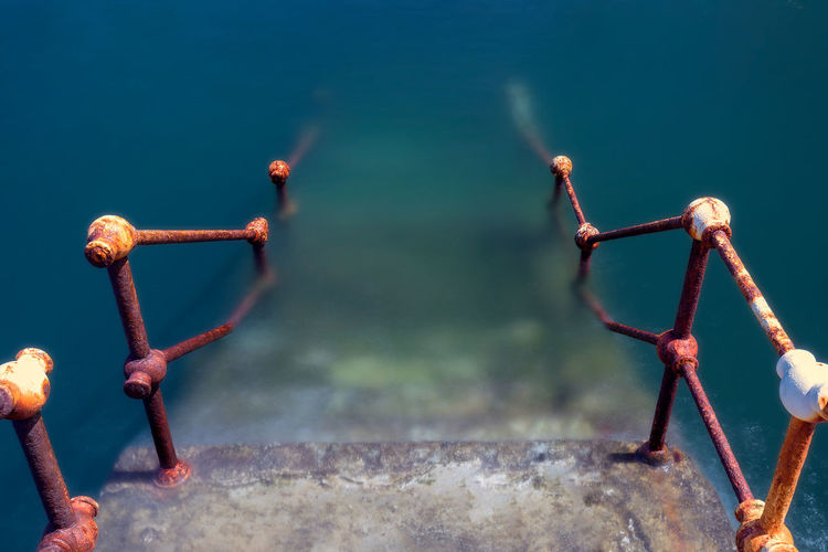 High angle view of rusty metal railing against sea