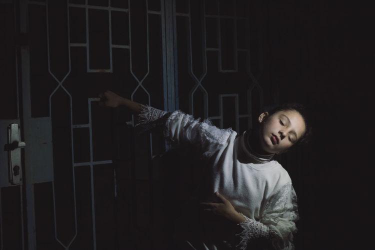 Full length of a girl standing against dark background