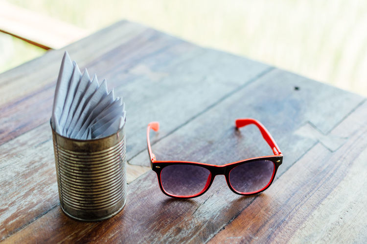 High angle view of sunglasses by tissue papers in container on wooden table