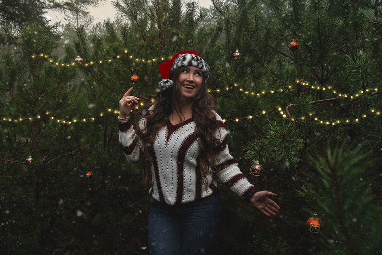 Portrait of a smiling young woman standing against christmas trees