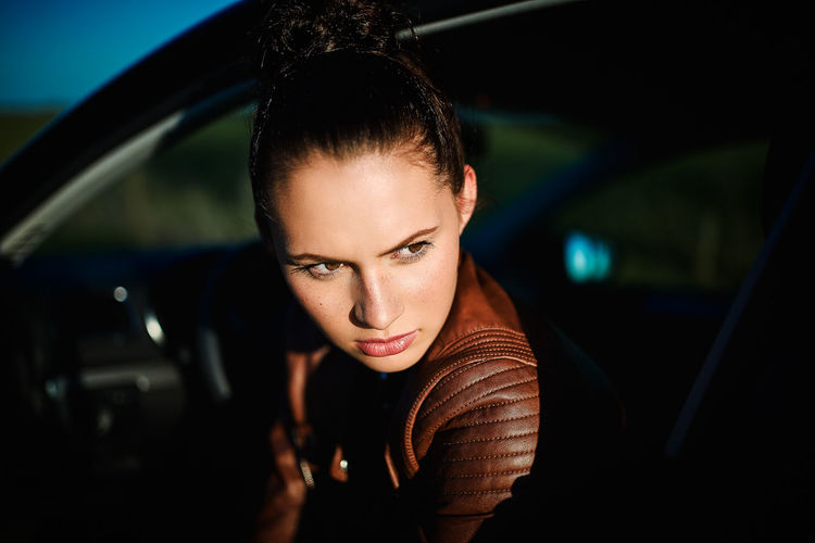 Portrait of young woman in car