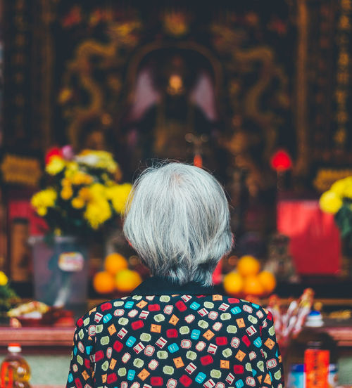 REAR VIEW OF WOMAN PRAYING IN TEMPLE