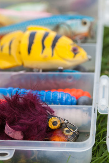 Close-up of multi colored fishing hooks in box
