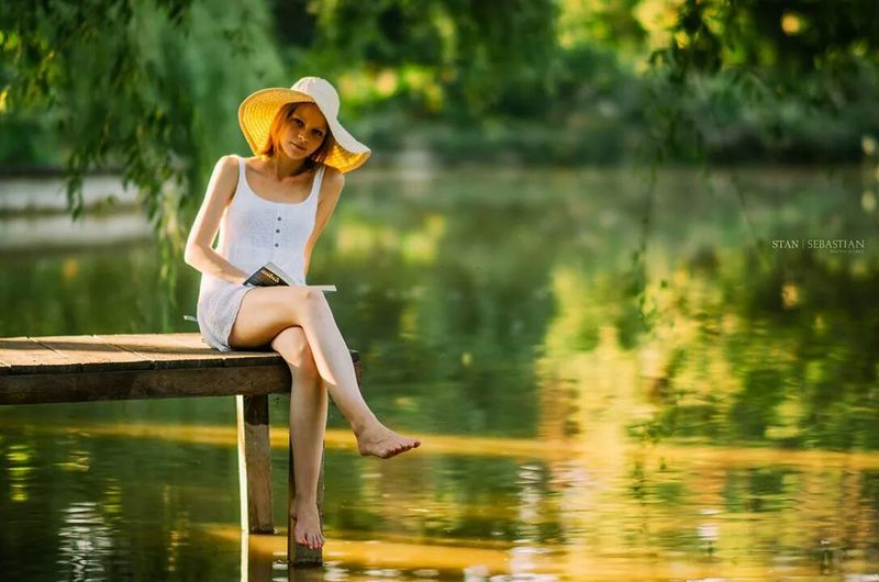 Portrait Of Young Woman Sitting On Pier Against Lake
