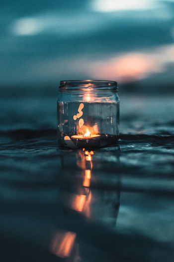 Candle Close-up Container Day Drink Floating On Water Glass - Material Illuminated Jar Lake Nature No People Orange Color Outdoors Reflection Refreshment Selective Focus Surface Level Transparent Water Waterfront