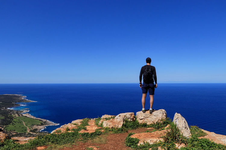 Rear view of man looking at sea against blue sky