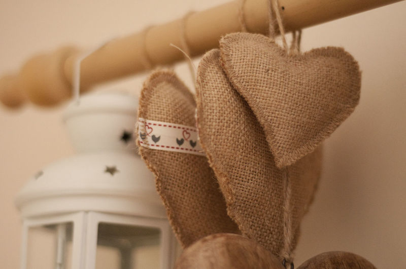 Close-Up Of Jute Hearts And Lantern Hanging On Rod Against Wall