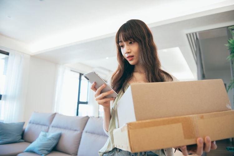 Young woman using mobile phone in box