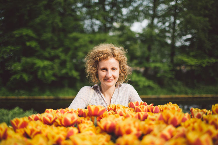 Netherlands Tulips Adult Beauty In Nature Curly Hair Day Emotion Flowering Plant Freshness Front View Girl Hair Hairstyle Happiness Headshot Looking At Camera Nature One Person Outdoors Plant Portrait Real People Selective Focus Smiling Spring Women