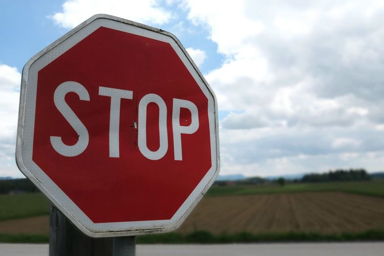Close-up of stop sign by field against sky