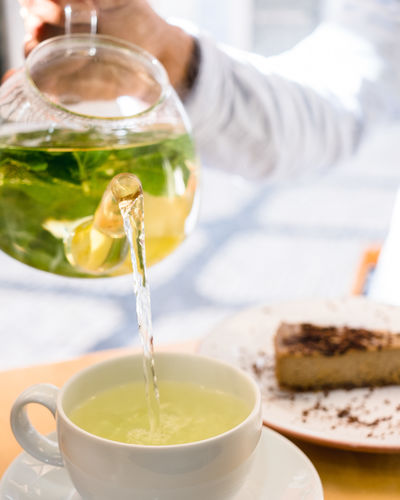 Food And Drink Food One Person Refreshment Drink Hand Human Hand Freshness Pouring Holding Cup Human Body Part Tea Indoors  Tea - Hot Drink Sweet Food Close-up Hot Drink Adult Tea Cup Herb Glass Teapot Crockery Mint Leaf - Culinary