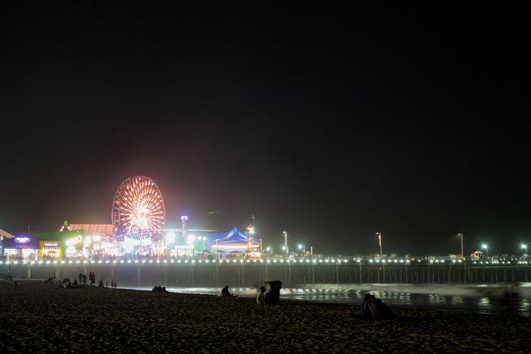 Illuminated Ferris Wheel By Santa Monica Pier At Night