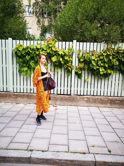 Full length portrait of girl standing on footpath against fence