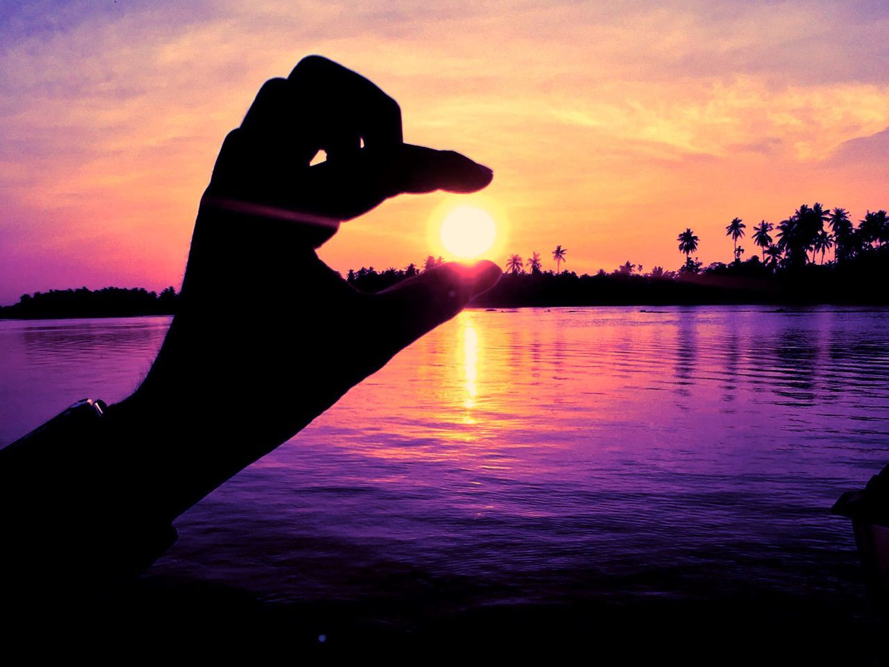 human hand, sunset, silhouette, human body part, human finger, water, beauty in nature, sky, nature, one person, real people, orange color, optical illusion, sun, outdoors, leisure activity, cloud - sky, lifestyles, scenics, close-up, sea, men, day, people