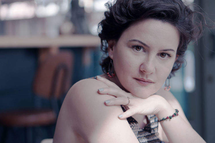 Close-Up Portrait Of Beautiful Mature Woman Sitting Indoors