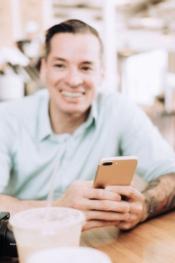 Portrait of smiling man using smart phone while sitting on table