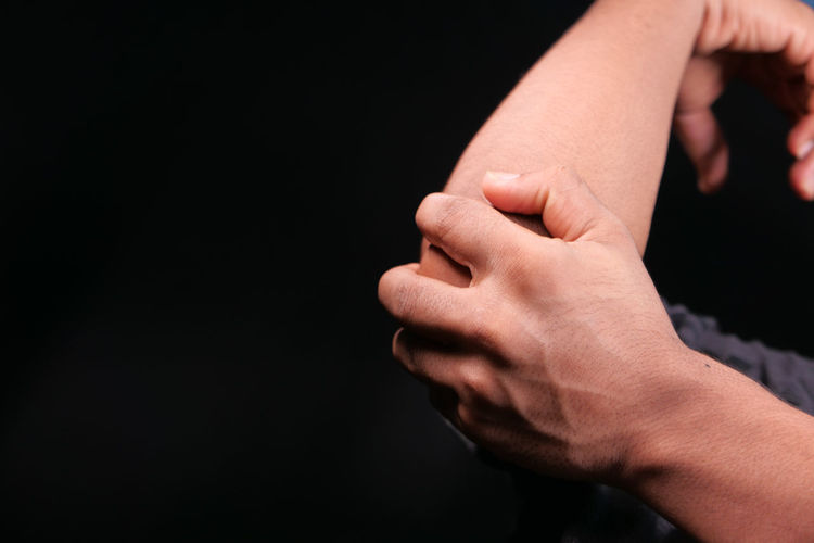 Close-up of hands touching hand over black background