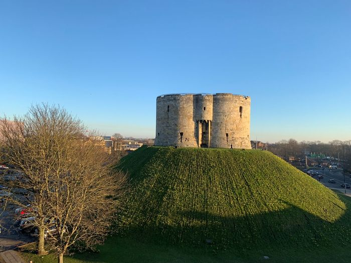 Clifford's Tower, York Clifford's Tower York Architecture Clear Sky Sky Built Structure Nature History The Past No People Building Exterior Day Sunlight Castle Blue Outdoors Ancient Fort Green Color