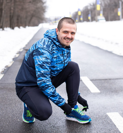 Smiling man tying shoelaces on running sneakers before run. Outdoor workout preparation Looking At Camera One Person Real People Full Length Smiling Portrait Lifestyles Clothing Winter Emotion Leisure Activity Day Happiness Road Young Adult Sitting Focus On Foreground Casual Clothing Outdoors Warm Clothing Running Sportsman Runner