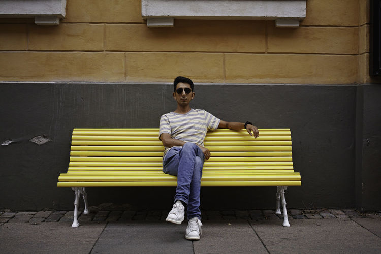 Portrait of man sitting on bench against wall