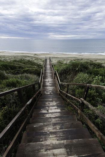 Walkway leading towards sea against sky