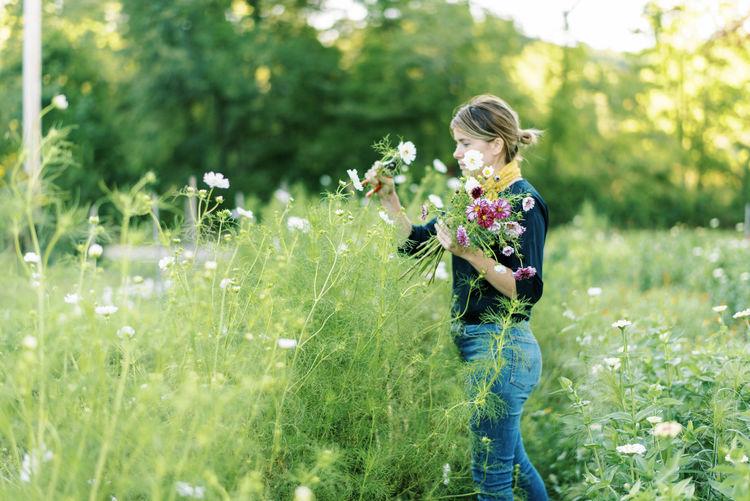 Full length of woman holding flower on field