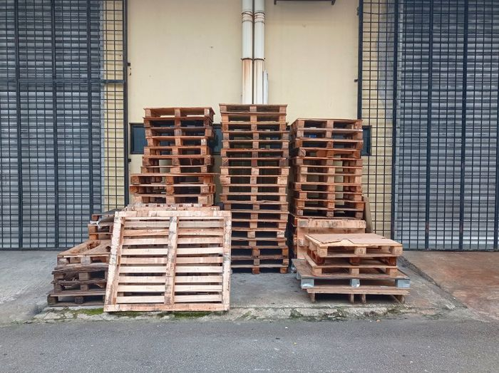 Stack of logs against building