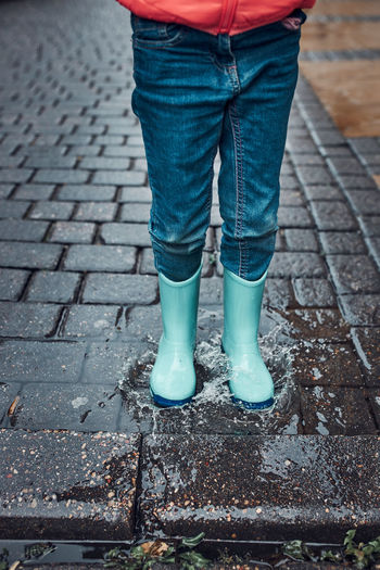 Close up of legs of little girl jumping in puddle wearing rubber boots walking in on rainy day