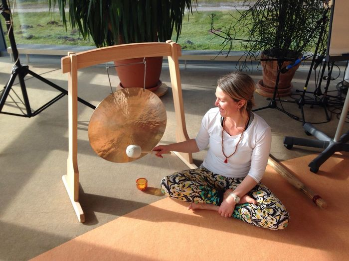 Girl with a gong Om Shanti Yoga Spirituality Meditation Sound Gong Only Women One Person Sunlight One Woman Only Day Casual Clothing Full Length Adults Only Working Shadow People Women Adult Sitting Young Adult