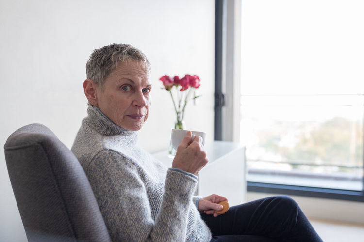 Older woman drinking tea by window Adult Casual Clothing Day Flower Focus On Foreground Glass - Material Holding Indoors  Lifestyles Looking At Camera One Person Plant Portrait Real People Sitting Smiling Transparent Window