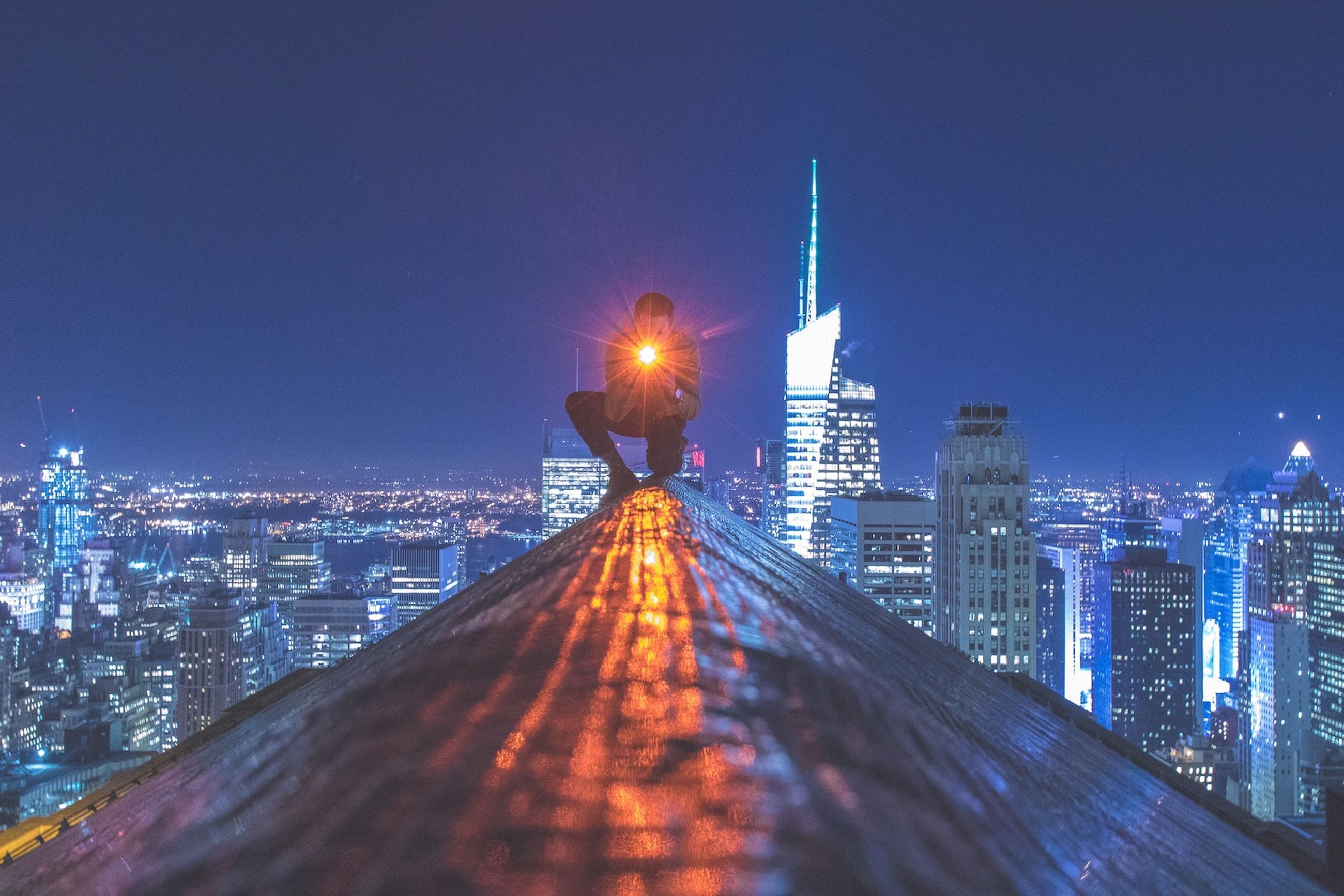 illuminated, architecture, built structure, city, building exterior, night, clear sky, cityscape, copy space, skyscraper, tall - high, blue, tower, the way forward, sky, capital cities, modern, street light, city life, bridge - man made structure
