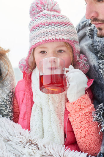 Cute Girl Drinking Tea With Father During Winter