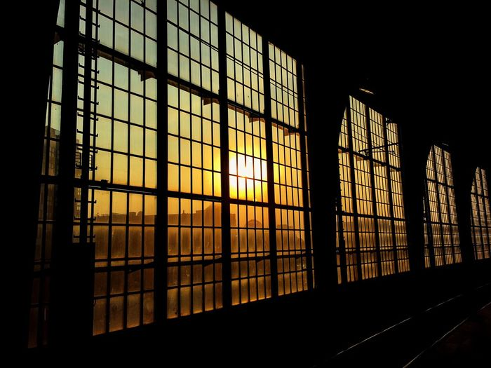 Sky during sunset seen through windows of railroad station