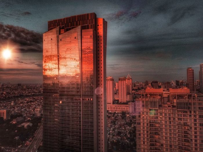 Digital composite image of buildings against sky during sunset