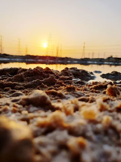 Surface level of rocks at beach against sky during sunset
