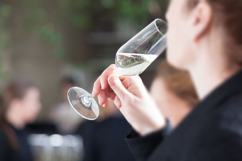 Midsection of woman drinking champagne while standing outdoors