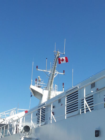 Blue Canada Flag Clear Sky Day Flag Low Angle View Mode Of Transport Nautical Vessel No People Outdoors Patriotism Sky Transportation