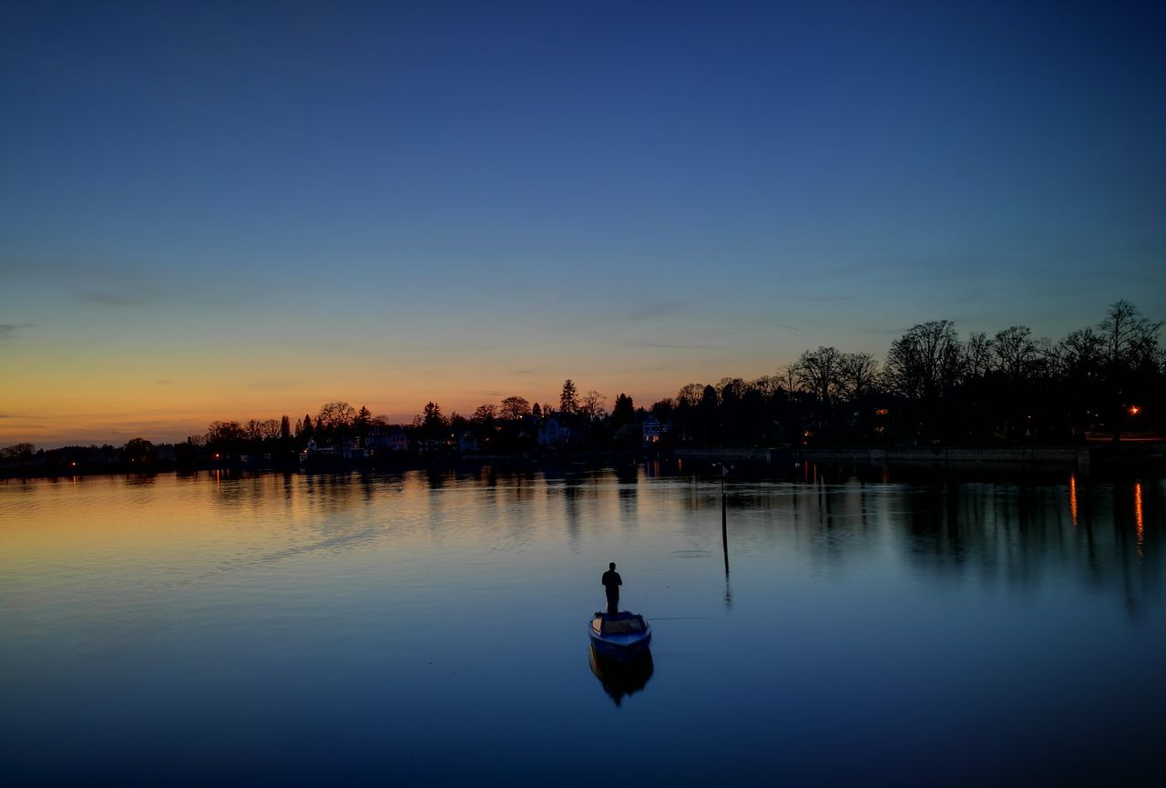sunset, silhouette, water, reflection, real people, waterfront, one person, outdoors, sky, nature, tree, blue, leisure activity, clear sky, beauty in nature, lake, architecture, men, building exterior, day, people