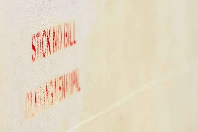 'Stick No Bill' Stencil spray painted in red to cream wall. No Posters Notice Painted Posters Red Sign Stencil Stencilled Stick No Bills Text Wall Warning Words No People Communication Close-up Wall - Building Feature Backgrounds Full Frame Selective Focus Paper Copy Space White Color Indoors  Pattern Creativity Western Script Orange Color Built Structure Still Life